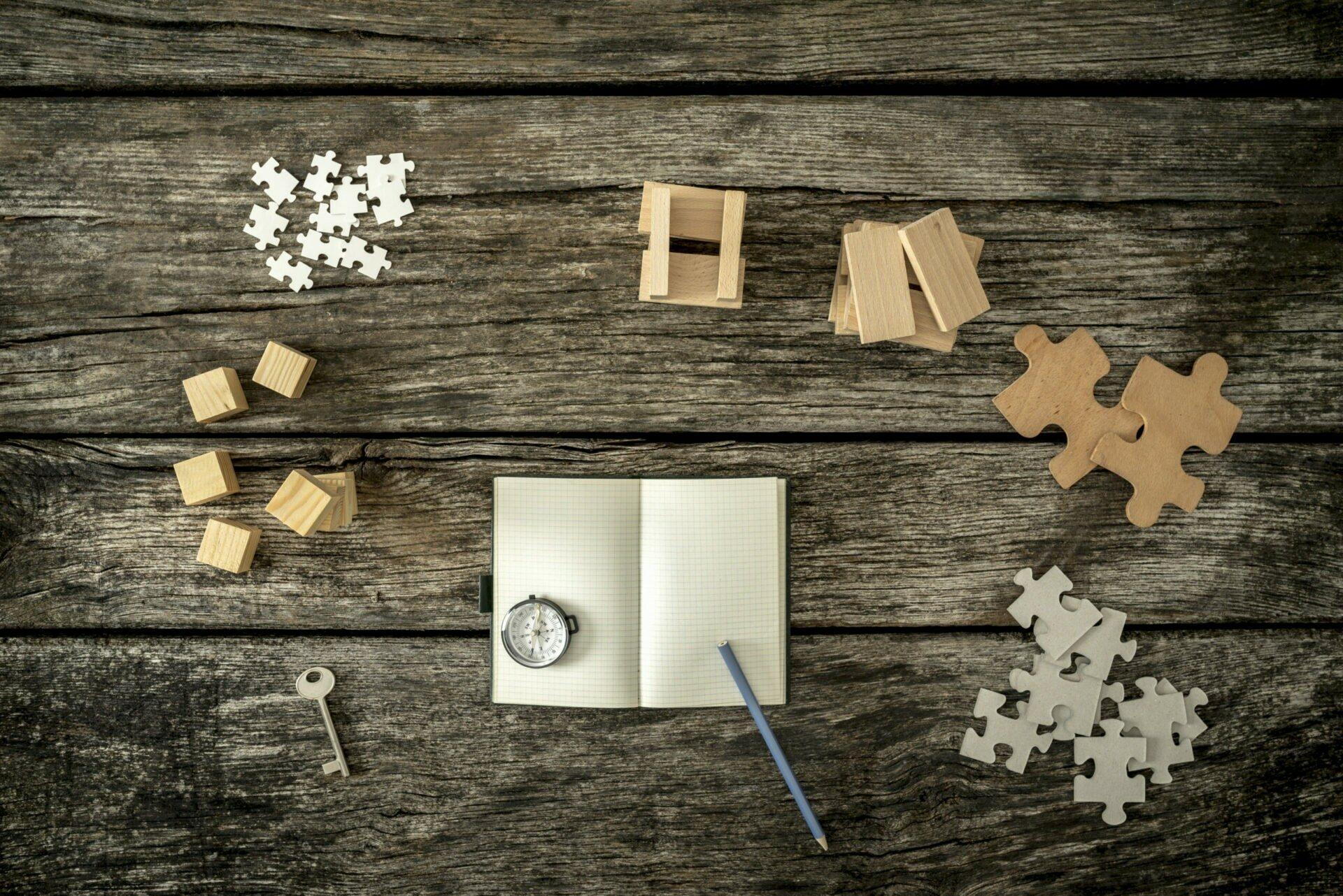 Blick von oben auf vershciedene Puzzlteile, Klötze, einen Schlüssel, ein Notizblock, einen Kompass und einen Bleistift.