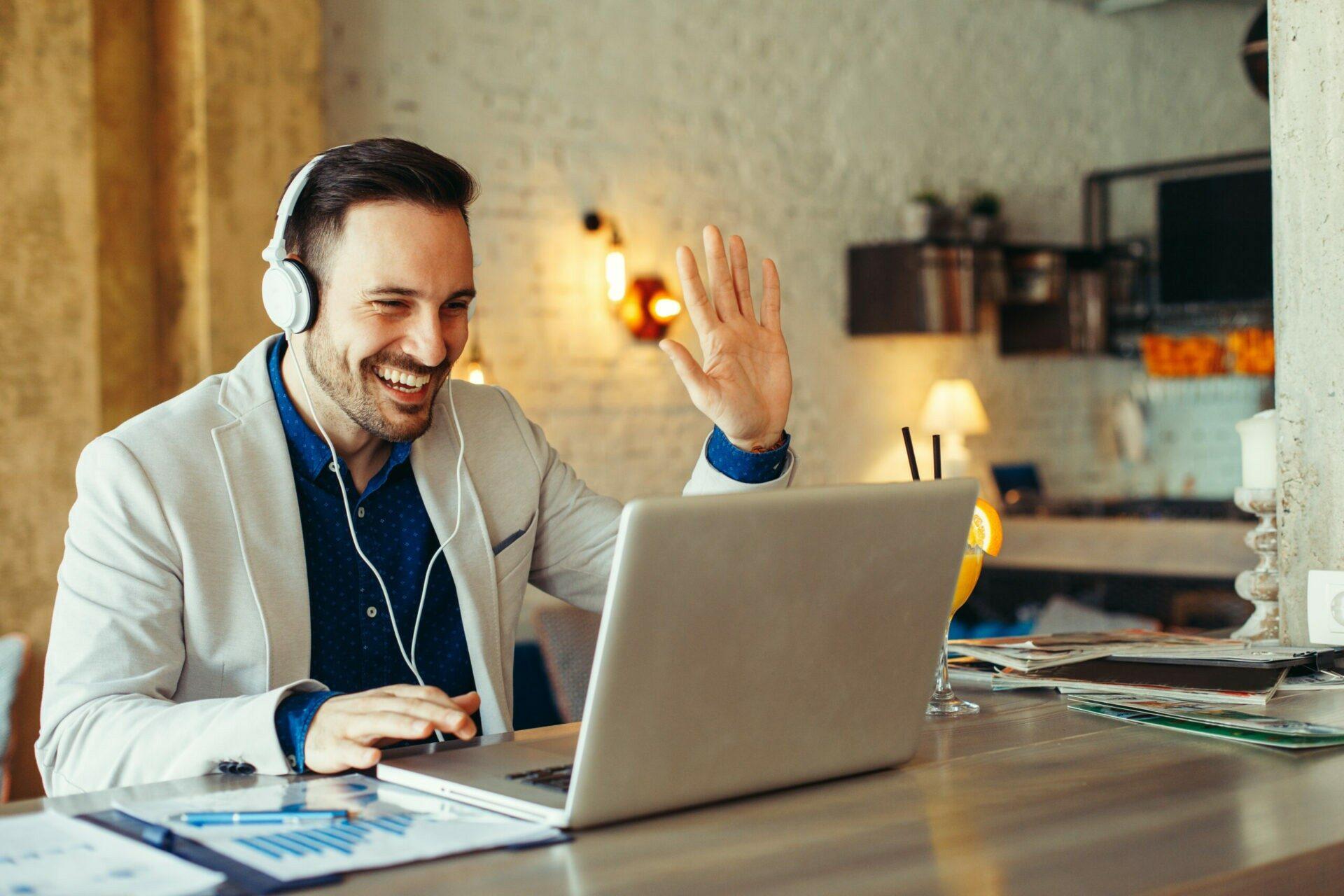 Ein Mann der in einer Videokonferenz lächelnd in seinen Laptop winkt.