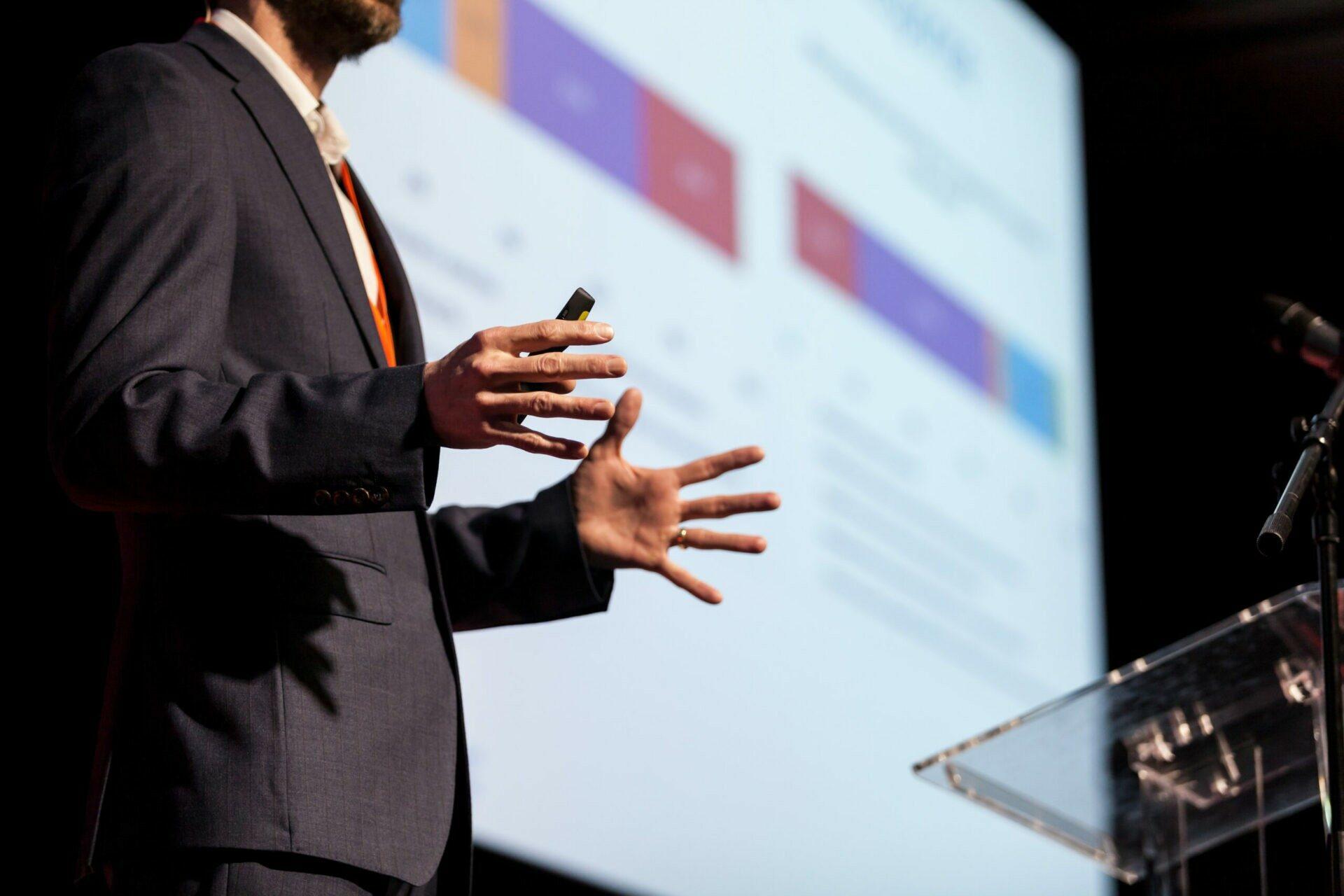 Die Hände eines Sprechers, der eine Präsentation auf einer Konferenz hält.