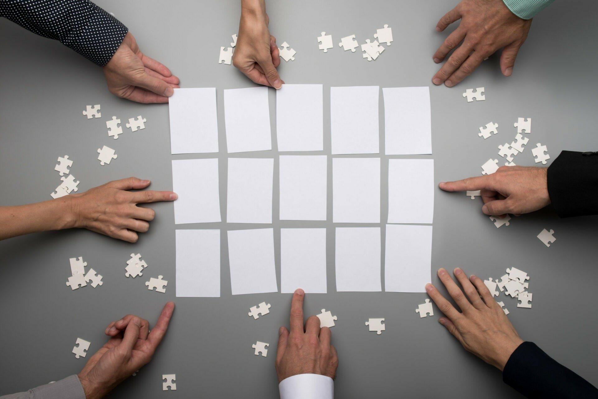 Fünfzehn Rechtecke die von Puzzleteilen umgeben sind. Acht verschiedene Hände greifen nach den Rechtecken.