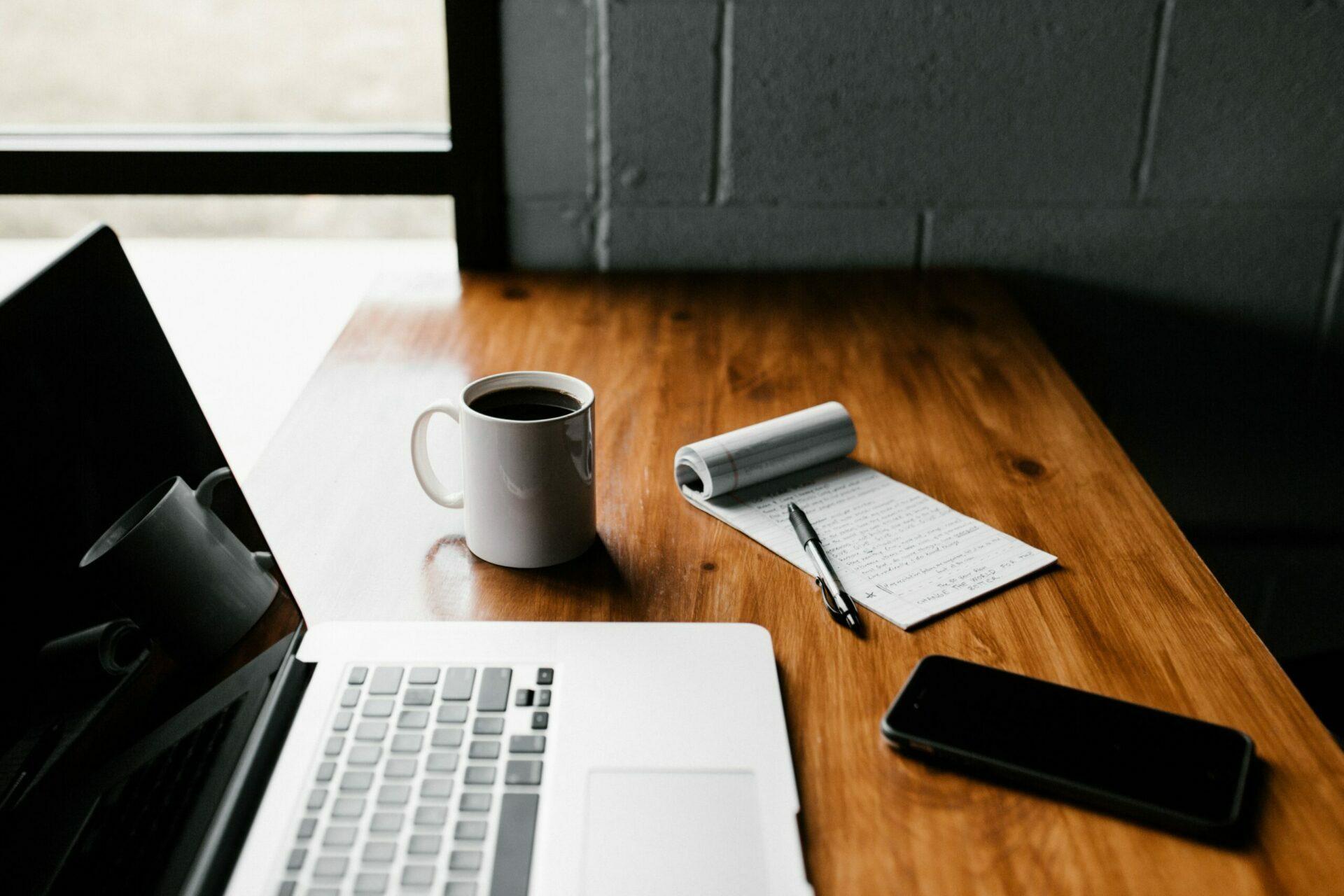 Ein Laptop, ein Notizblock, ein Stift, ein Handy und eine Tasse Kaffee auf einem Schreibtisch.