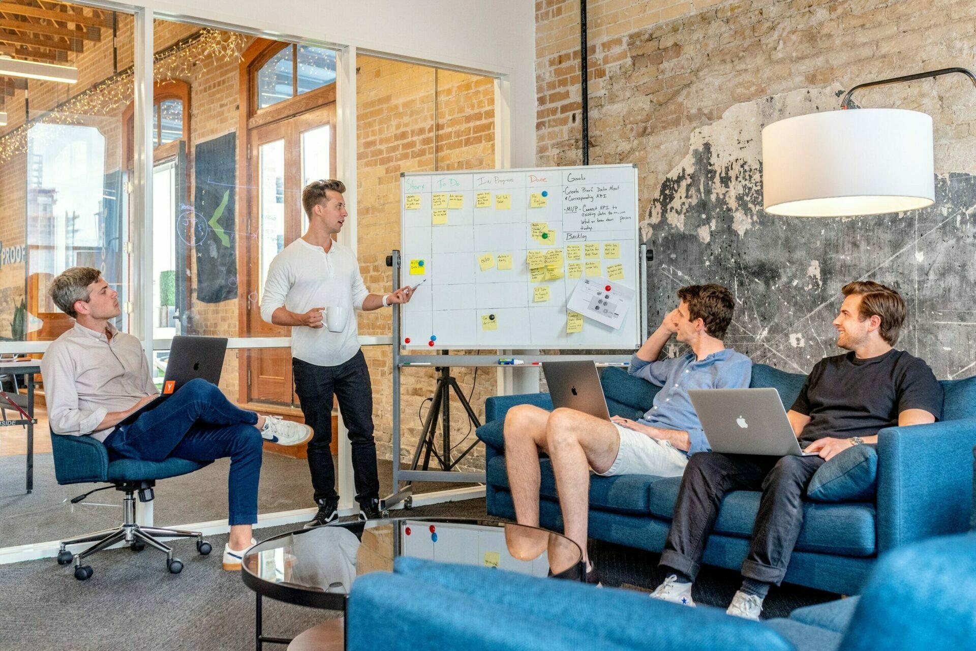 Vier junge Männer in legerer Kleidung in einem Business-Meeting.