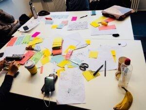 Zusammengestellte Tische, auf denen Papier, Schere, Stifte und Haftnotizen sind. Es wird an einem Projekt gearbeitet.