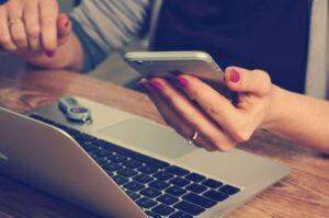 Foto eines Laptops, vor dem eine Frau sitzt. Es sind nur die Hände im Bild, die ein Handy halten.