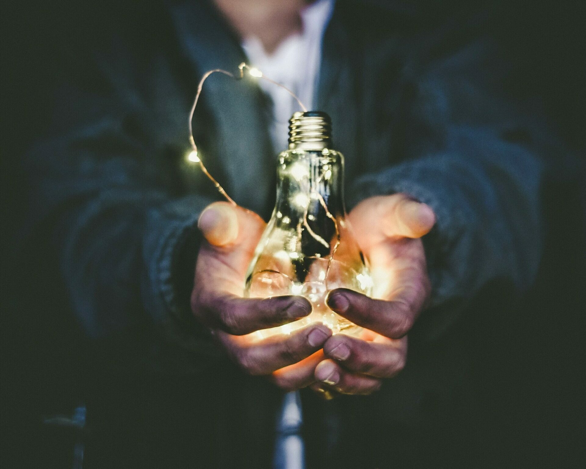 Glowing bulb in the hands of a man