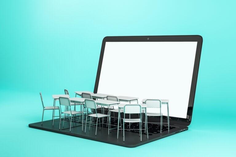 Foto zum Thema Online Unterricht. Laptop vor türkisfarbigem Hintergrund. Auf der Tastatur steht eine Klassenzimmer-Einrichtung.