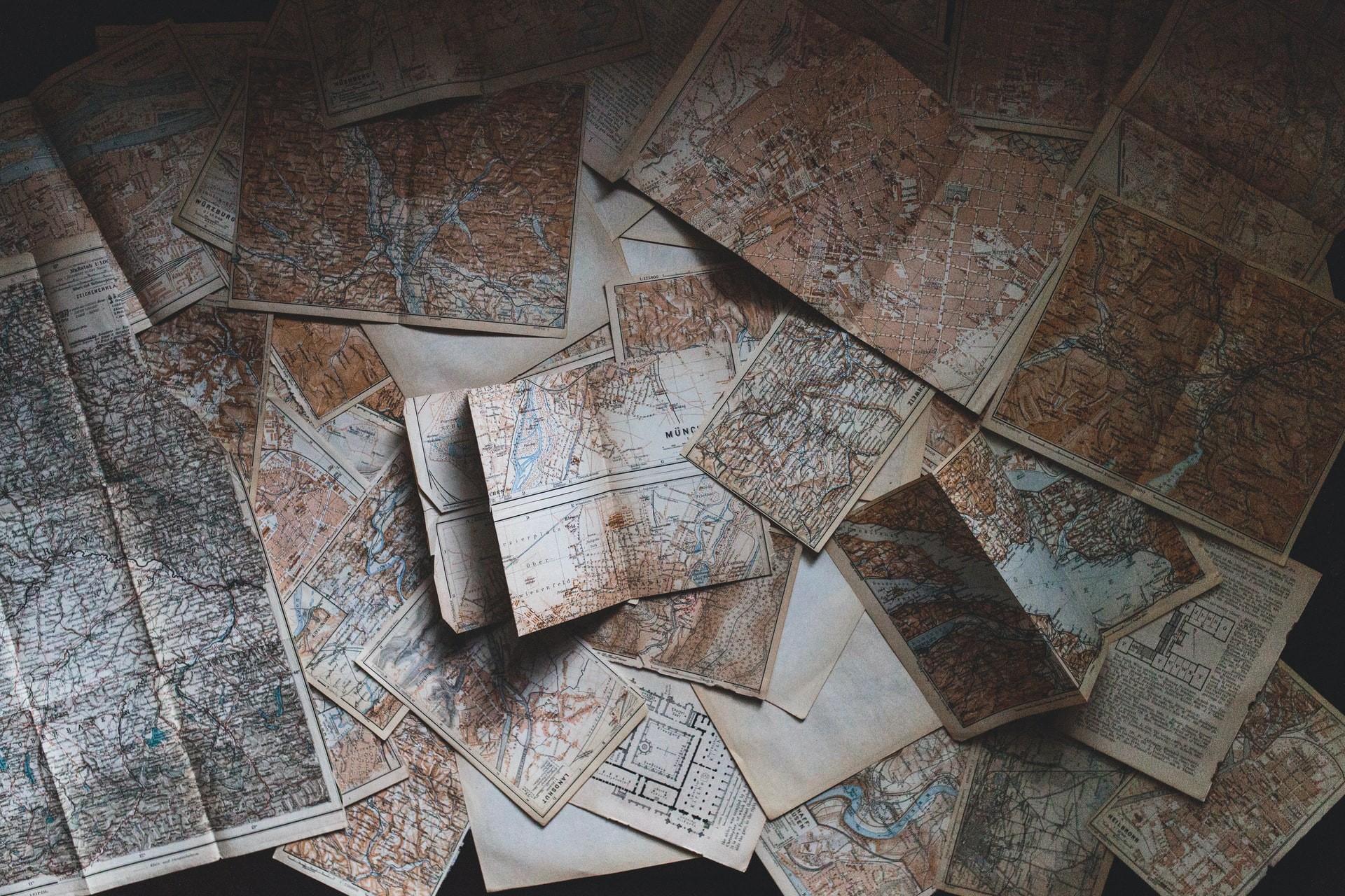 Foto aus der Vogelperspektive auf eine Viezahl ausgebreiteter Landkarten.