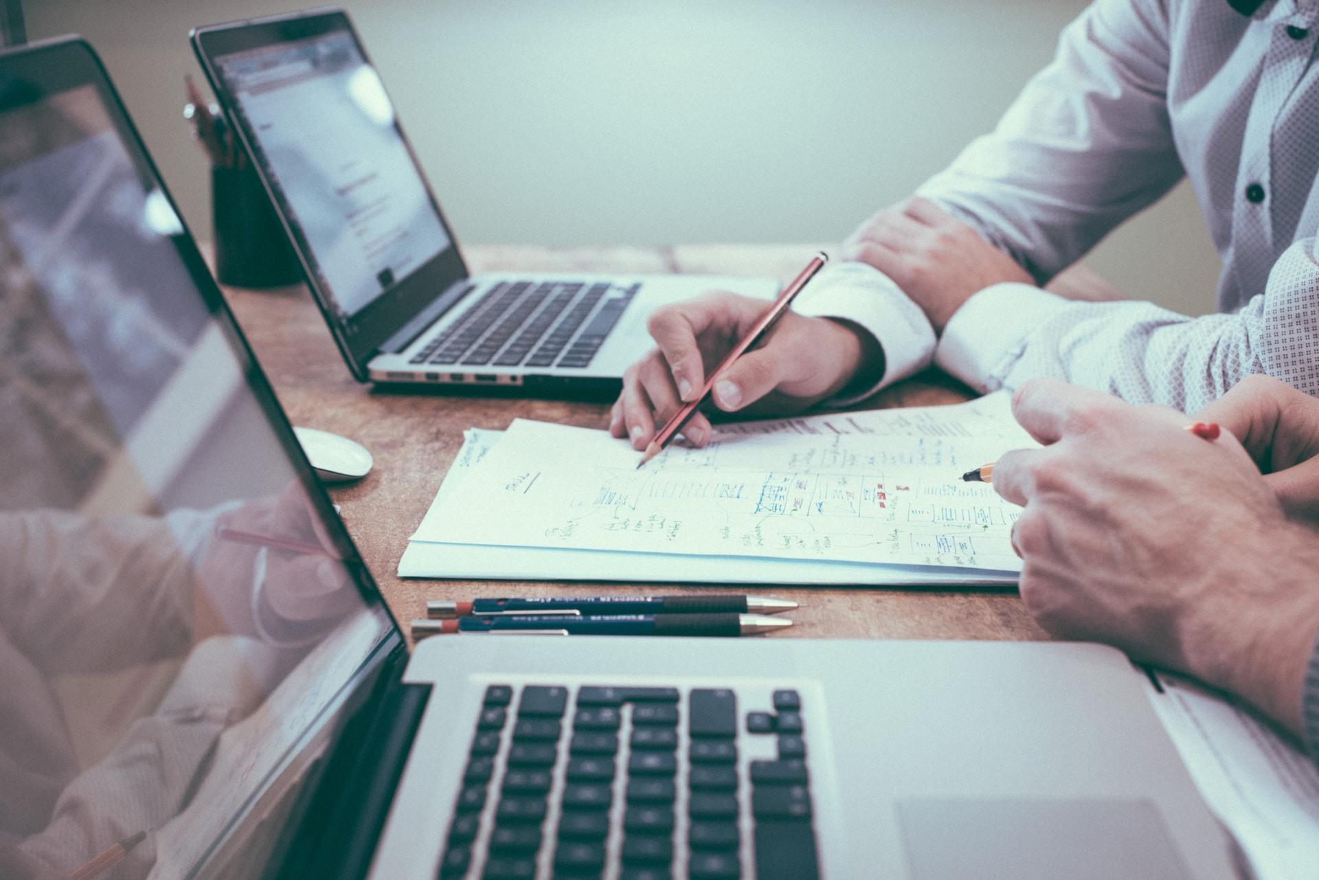 Foto eines Schreibtischs, auf dem zwei Laptops stehen. Zwei Männerhände arbeiten in deren Mitte an einem Dokument.