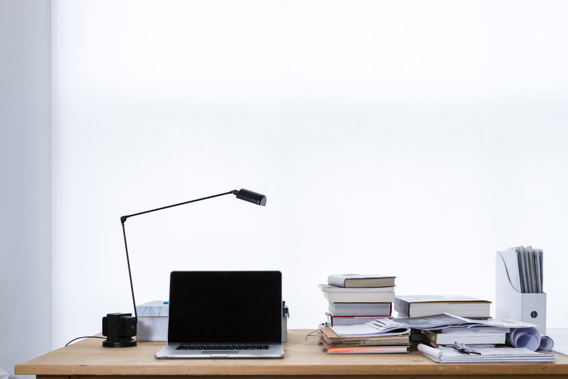 Foto eines Schreibtischs, auf dem ein Laptop sowie Bücher, Dokumente und Ordner liegen.