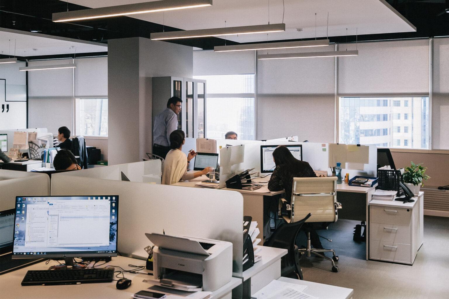 Eine Gruppe Mitarbeiter im Gespräch im Büro. Foto zum Thema Wissensmanagement für Unternehmen.
