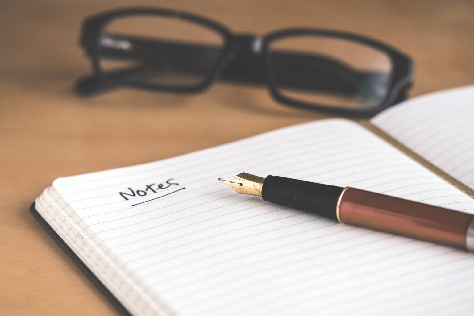 Foto von einem aufgeschlagenen Notizbuch. Es steht mit Füller das Wort Notizen darin.