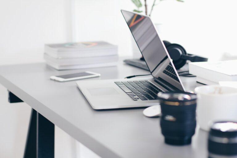 Foto von einem Schreibtisch mit Laptop, Kffeetasse, Büchern und weiteren Arbeitsmaterialien.