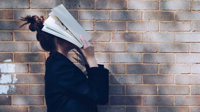 Foto zum Thema Lernen: Junge Frau vergräbt ihr Gesicht in einem Buch.