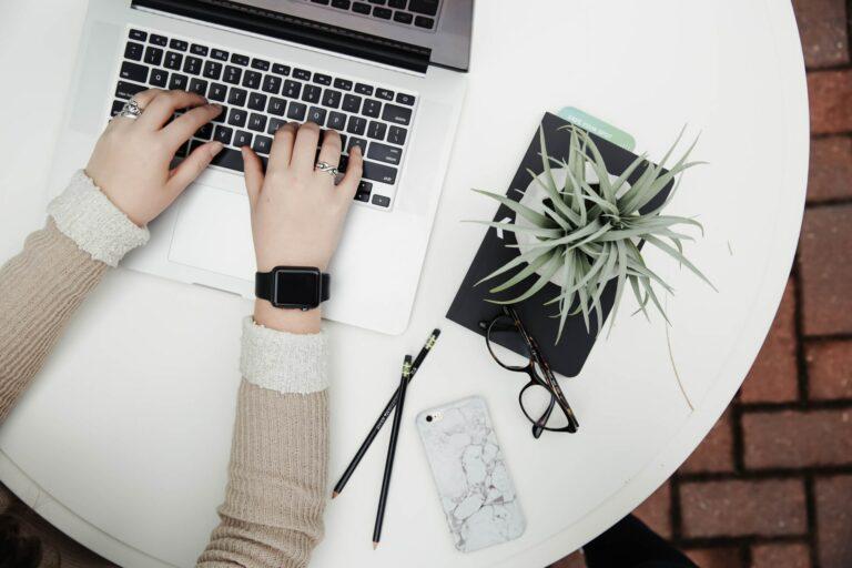Foto Vogelperspektive auf einen Tisch mit Laptop, an dem eine junge Frau arbeitet. Es sind nur ihre Hände und Unterarme abgebildet.